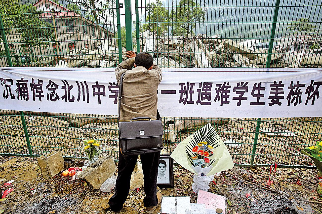 汶川大地震暴露校舍建築疑偷工減料,支柱幼細、鋼筋數量少、混凝土質量差等問題。圖為倒塌的北川中學校舍,造成約一千名師生死亡,一名父親在震後一周年哀悼死去的兒子。(Feng Li/Getty Images)