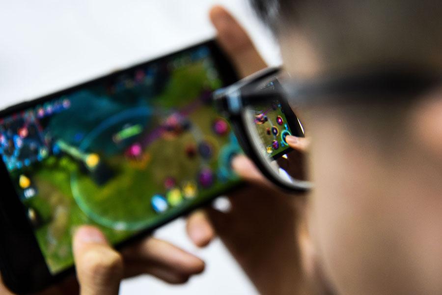 網絡遊戲盛行,許多中共領導幹部也沉迷於此。圖為一名男子正在玩手機遊戲。(CHANDAN KHANNA/AFP/Getty Images)