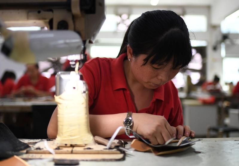 由於經濟活動擴張勢頭減弱,中國製造業及服務業9月的PMI雙雙下跌。圖為廣東東莞的一家製鞋工廠。(GREG BAKER/AFP/Getty Images)