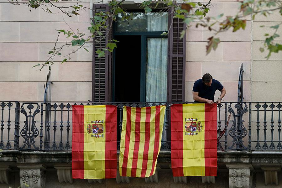 圖為10月10日,巴塞隆拿一名男子在露台上掛起西班牙和加泰羅尼亞旗幟。(PAU BARRENA/AFP/Getty Images)