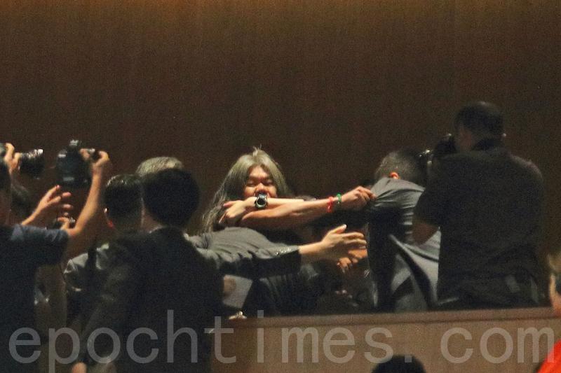 圖說:林鄭步入議事廳後,早前被取消議員資格的社民連梁國雄在觀眾席叫口號,被多名保安帶離觀眾席。(李逸/大紀元)