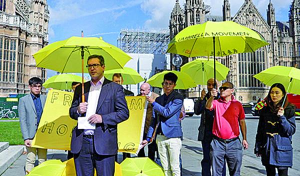 2017年9月28日,英國議會大廈前,羅哲斯(前左一)在香港雨傘運動三周年集會上發言。(大紀元資料圖片)