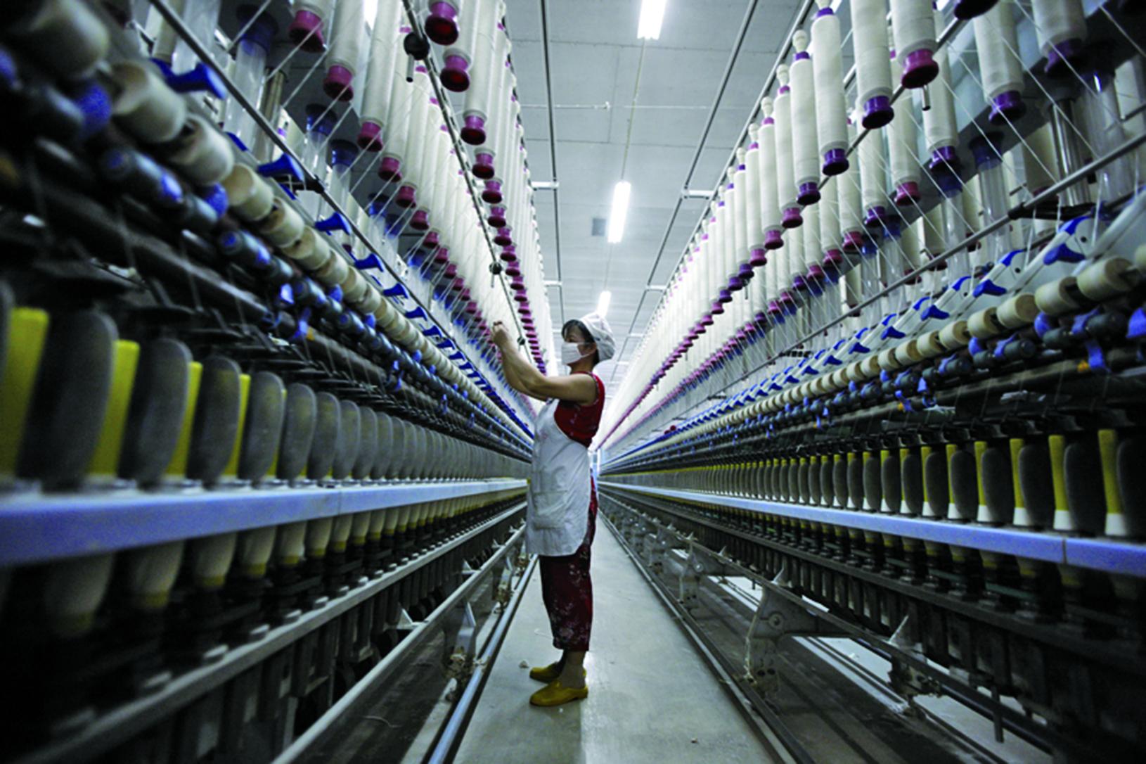 國際學者日前預測「十九大」後,大陸經濟政策不會大變。圖為淮北一家紡織廠。(AFP)