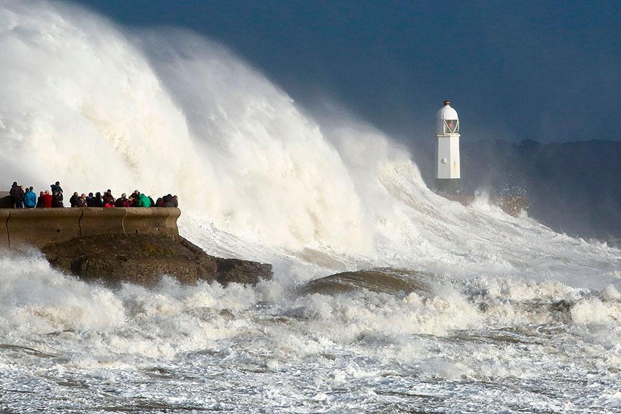 圖為民眾在當地時間周一(10月16日)到威斯爾南部海邊感受颶風奧菲利雅造成的巨浪。(GEOFF CADDICK/AFP/Getty Images)