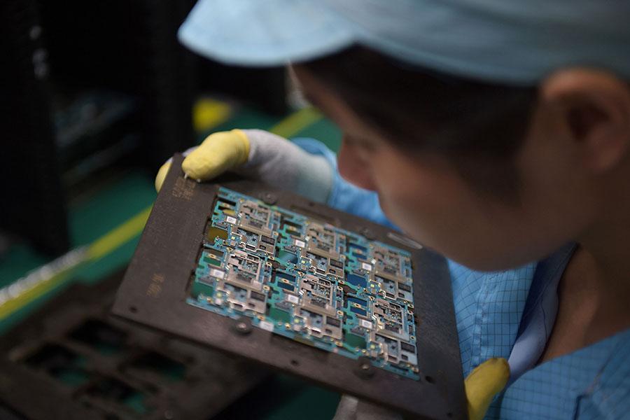 特朗普政府已開始對中國的知識產權問題進行「301調查」,調查或許是為11月訪華做前期準備。圖為一名東莞工人正在查看手機晶片。(NICOLAS ASFOURI/AFP/Getty Images)