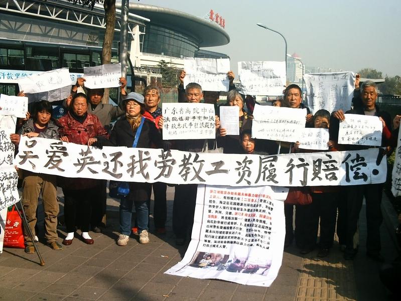 2013年11月6日中午一批曾經被非法勞教的在京訪民在北京南站南廣場打出橫幅,強烈要求司法部長吳愛英履行國家賠償法,補償勞教工資。(網絡圖片)