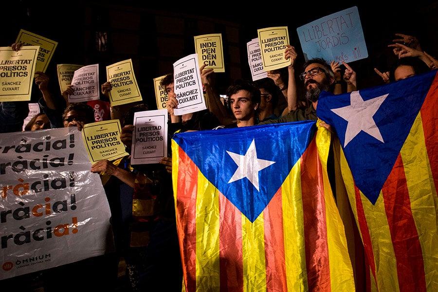 10月17日凌晨,數百名獨派支持群眾聚集在自治區政府辦公室外,有人高唱加泰羅尼亞國歌,並舉著寫有「釋放政治犯」的標語。(PAU BARRENA/AFP/Getty Images)