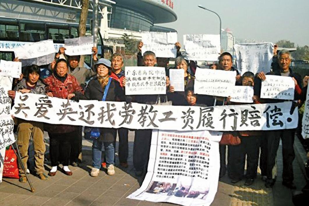 2013年11月6日,一批曾被非法勞教的訪民在北京南站南廣場打出橫幅,強烈要求當時的司法部長吳愛英賠償勞教工資。(網絡圖片)