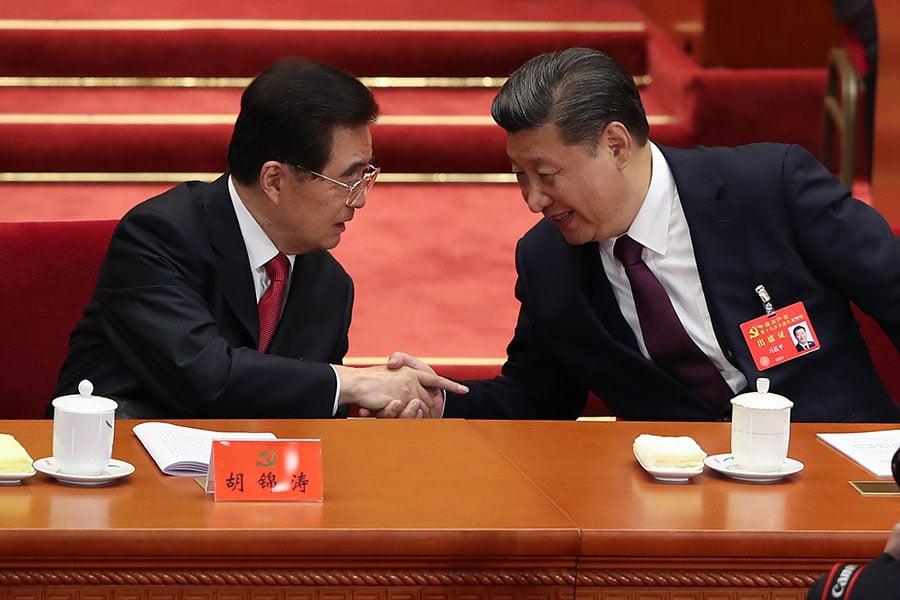 習近平在宣讀完報告回到座位上時,與在旁的胡錦濤握手和談笑風生。(Lintao Zhang/Getty Images)