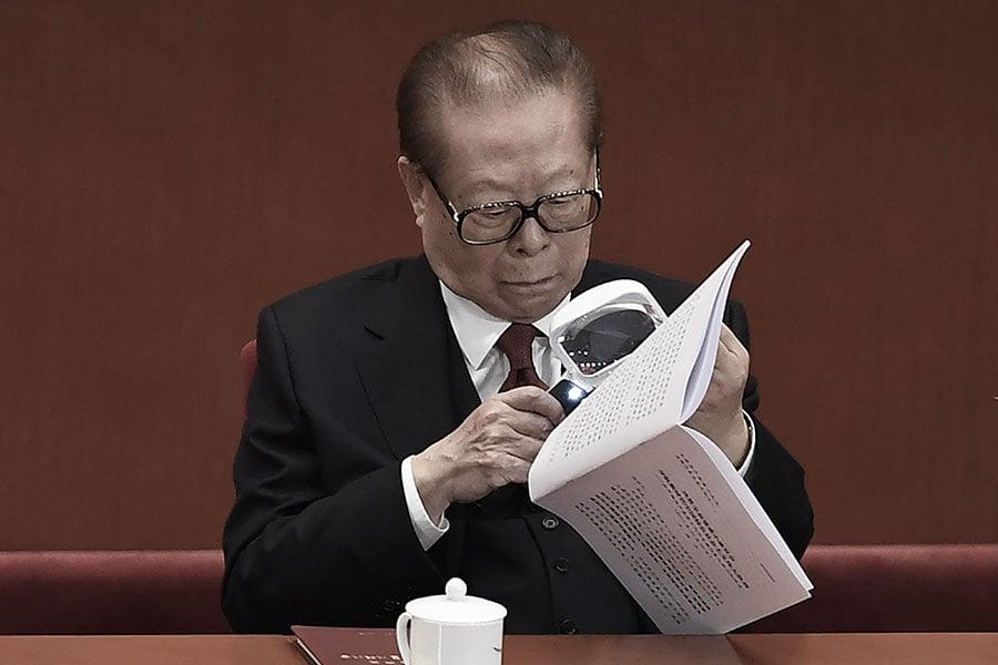 圖為10月18日十九大開幕上,江澤民拿著一個放大鏡來輔助看十九大報告內容。(WANG ZHAO/AFP/Getty Images)