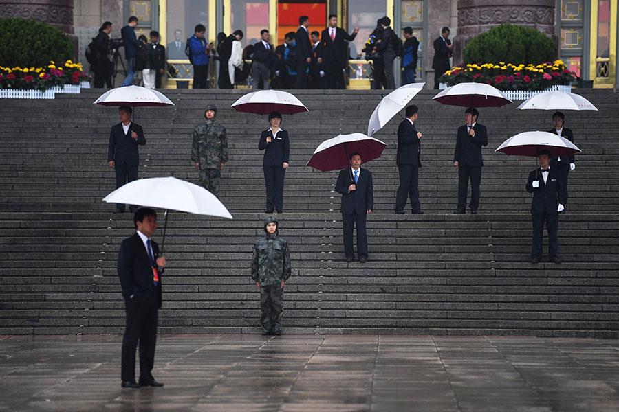中共十九大於10月18日在北京的秋風凄雨中開幕。圖為保安人員撐著雨等待代表到來。(AFP PHOTO / Greg Baker)