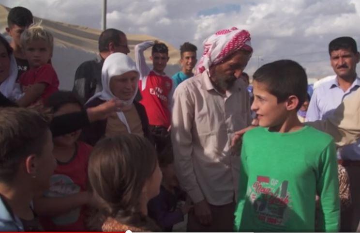 據庫爾德斯坦地區政府(KRG)綁架救援辦公室的信息,目前大約有3000多人仍在IS的手中,其中大多數是婦女和兒童。圖中綠衫男孩剛被從IS手中救出,回到親人身邊。(視像擷圖)