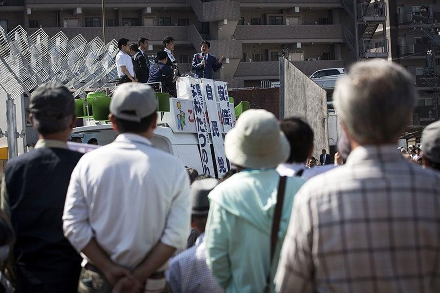 日本國會眾議院選舉期間,在街頭,人們在聆聽候選人的演講。圖為10月11日,日本首相、自民黨黨魁安倍晉三在靜岡縣燒津市為自民黨候選人站台。(BEHROUZ MEHRI/AFP/Getty Images)