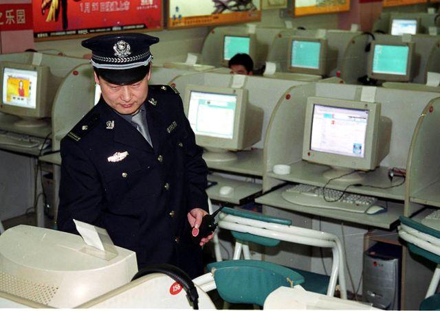 中共耗資加大控制網絡。圖為警察在北京一家網吧裏巡邏。(法新社)