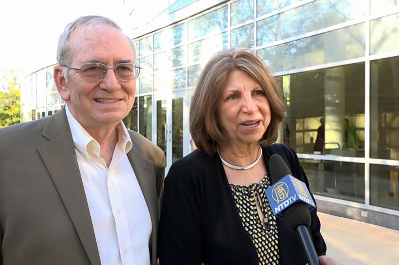 語言學教授Charlene Rivera(右)和Charles Stansfield(左)一同欣賞神韻交響樂團的演奏,他們感到演出中包含了巨大能量。(新唐人電視台)