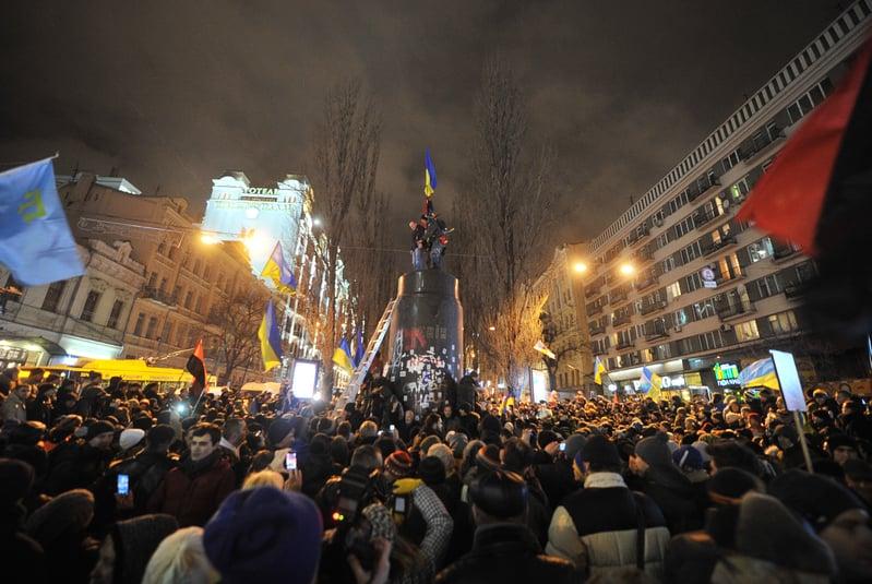 從10月21日開始,波蘭新修訂的去共產主義法生效。圖為2013年12月8日烏克蘭基輔,市中心的一座列寧塑像被推倒後,民眾歡呼慶祝。烏克蘭民眾近年來在全國掀起推倒列寧雕像的棄共行動。(GENYA SAVILOV/AFP)