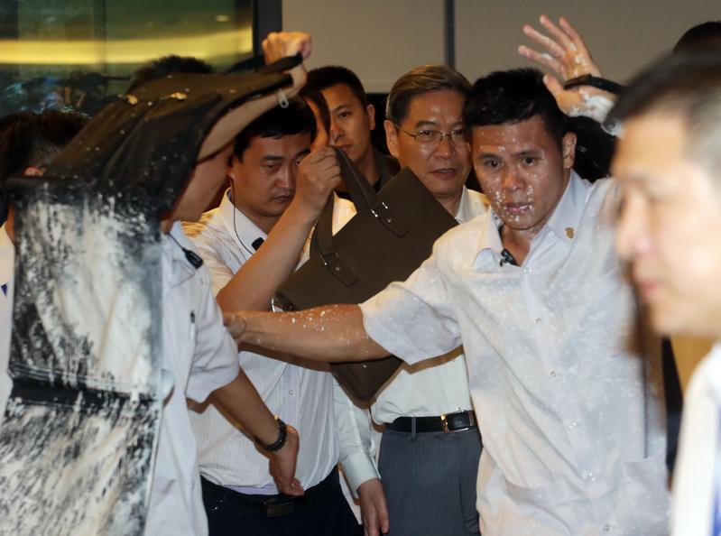 2014年6月中共國台辦主任張志軍(右三)與台灣行政院大陸委員會主委王郁琦在高雄中山大學茶敘,有抗議民眾在張志軍入場時潑白漆抗議,張志軍的維安人員被波及。(中央社)
