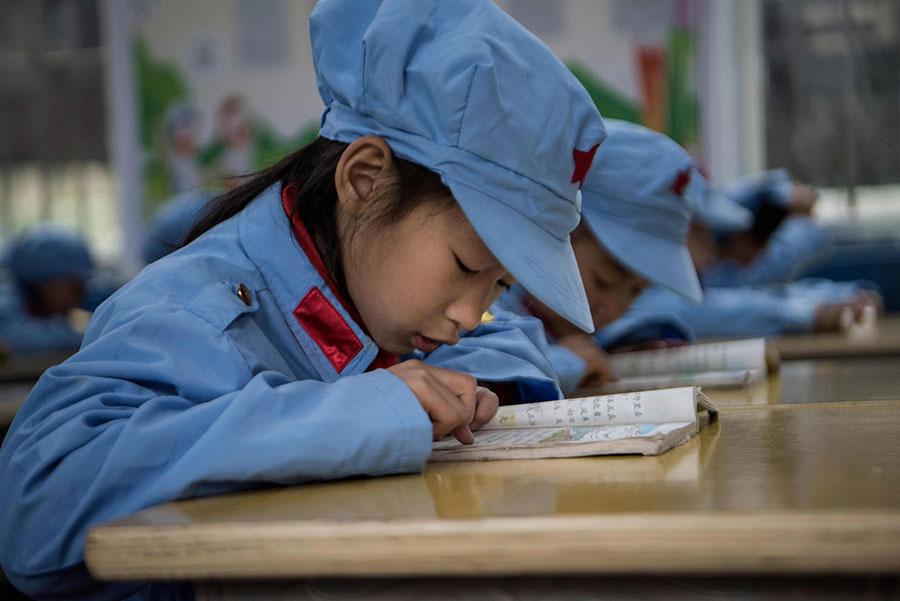 圖為貴州省一間小學,學生正在閱讀課本。(FRED DUFOUR/AFP/Getty Images)