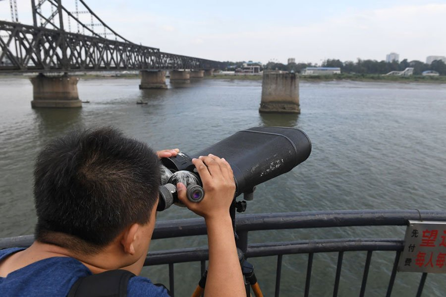 中朝邊境,遼寧丹東鴨綠江斷橋上一人用望遠鏡觀察對岸的北韓一方。(GREG BAKER/AFP/Getty Images)