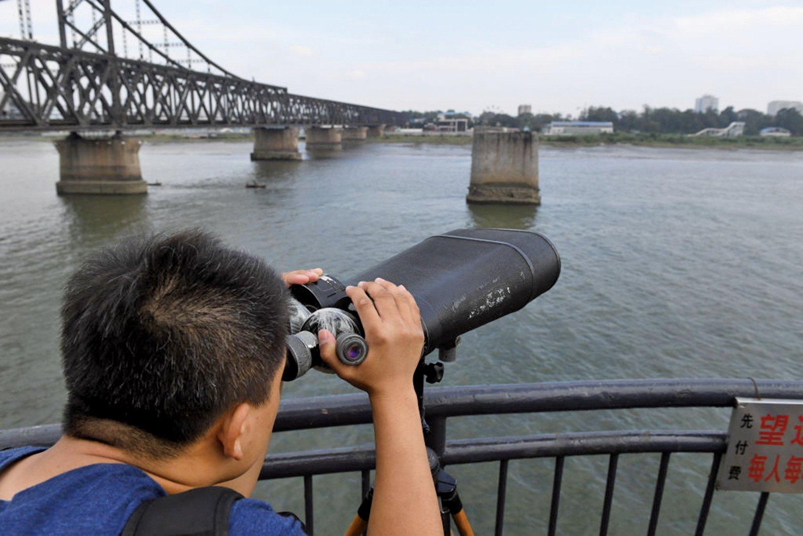 中朝邊境,遼寧丹東鴨綠江斷橋上一人用望遠鏡觀察對岸的北韓一方。(Getty Images)