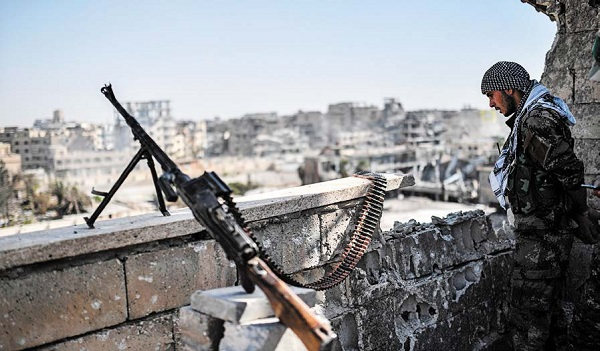 圖為一名抵抗IS的戰士在敘利亞城市拉卡守衛重新奪回的陣地。(Jack Taylor/Getty Images)