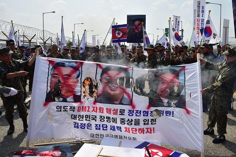 北韓獨裁者金正恩今年2月疑下令殺害從未謀面的同父異母哥哥金正男,令外界震驚,也讓人不免好奇,在其專制統治下,隱藏在他背後的兄弟姐妹,過著甚麼樣的生活。圖為南韓人2015年8月在街上焚燒北韓金氏政權三代領導人的肖像。(JUNG YEON-JE/AFP/Getty Images)