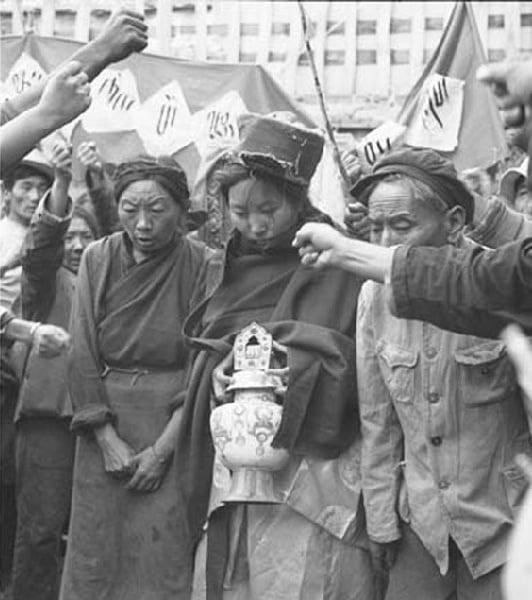 文革時期,中共當局在西藏發動批鬥會。圖中這個手捧寶瓶的年輕女子是西藏最著名的女活佛——桑頂・多吉帕姆・德欽曲珍。跟她一起被批鬥的老人是她的父母。這樣的場面在當時的拉薩幾乎每天可見。(網絡圖片)