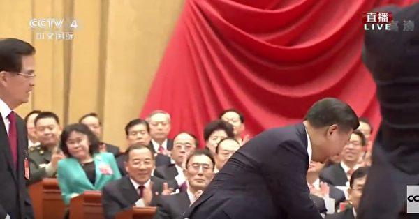 習近平宣讀完中共十九大報告後,他回到主席台與胡錦濤握手,並和胡錦濤談笑風生。但官媒沒有給出習與江握手畫面,江完全被攝影師遮住看不見人。(視像擷圖)