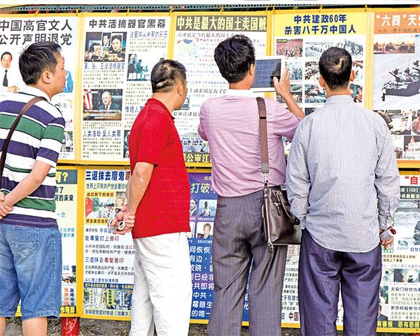 隨著中國民眾在國內和海外了解到中共殘酷鎮壓法輪功的真相,越來越多人選擇退出中共黨、團、隊組織,拒絕助紂為虐。圖為到海外旅遊的中國民眾觀看法輪功真相展板。(明慧網)