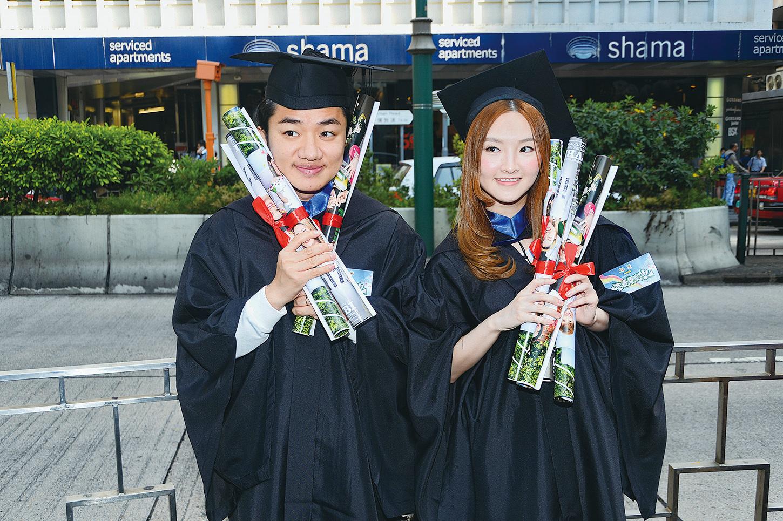 王祖藍和林欣彤穿畢業袍街頭宣傳《老表,畢業喇!》。(宋碧龍/大紀元)