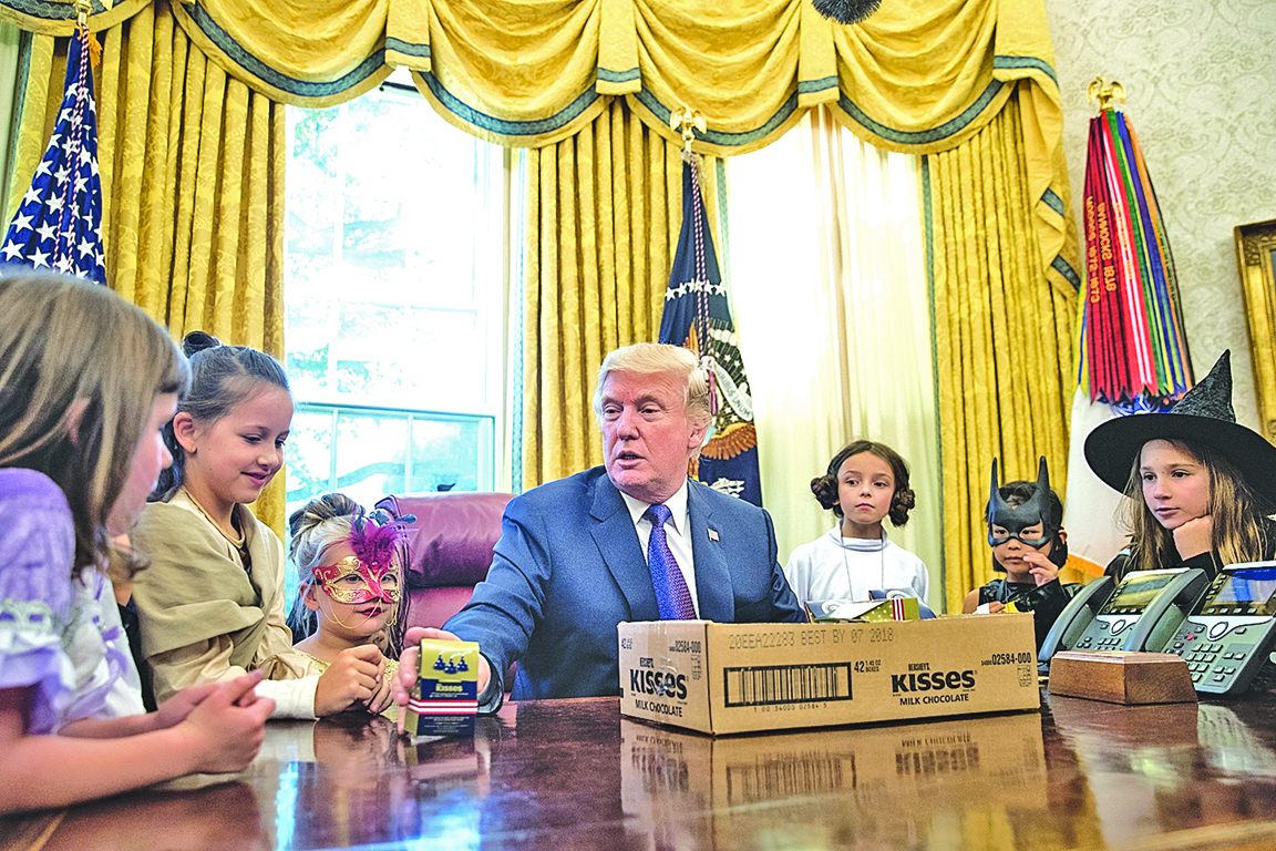 特朗普27日在白宮給新聞記者的孩子們發糖。(Getty Images)