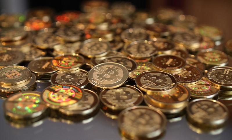 交易網站比特幣中國原定10月30日中午12時停止提現/提幣,但又發公告表示可以繼續提供提現/提幣服務。(George Frey/Getty Images)