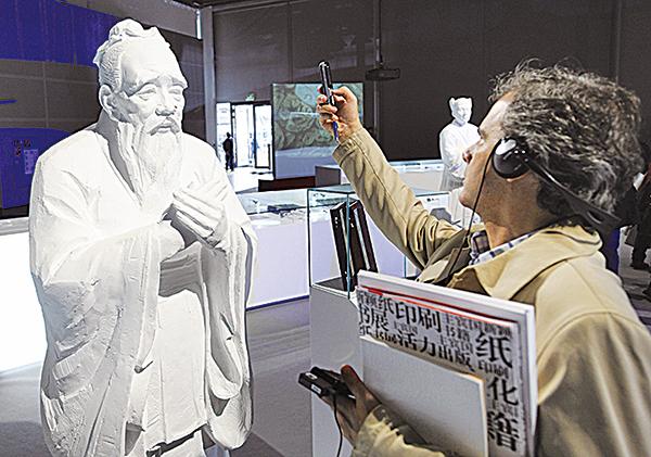 孔子的倫理思想和治國學說影響歐美思想界極深。圖為2009年法蘭克福書展中國館中,一名西方人用手機拍攝孔子雕像。(AFP)