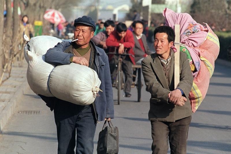 近日,大陸媒體稱農村土地承包制修改草案將被提請人大初審,聲稱農民會獲益。但是有評論認為,只要中共一黨專制在,農民就不可能真正獲益。圖為北京街頭為謀生而離開農村的農民工。(ROBYN BECK/AFP/Getty Images)