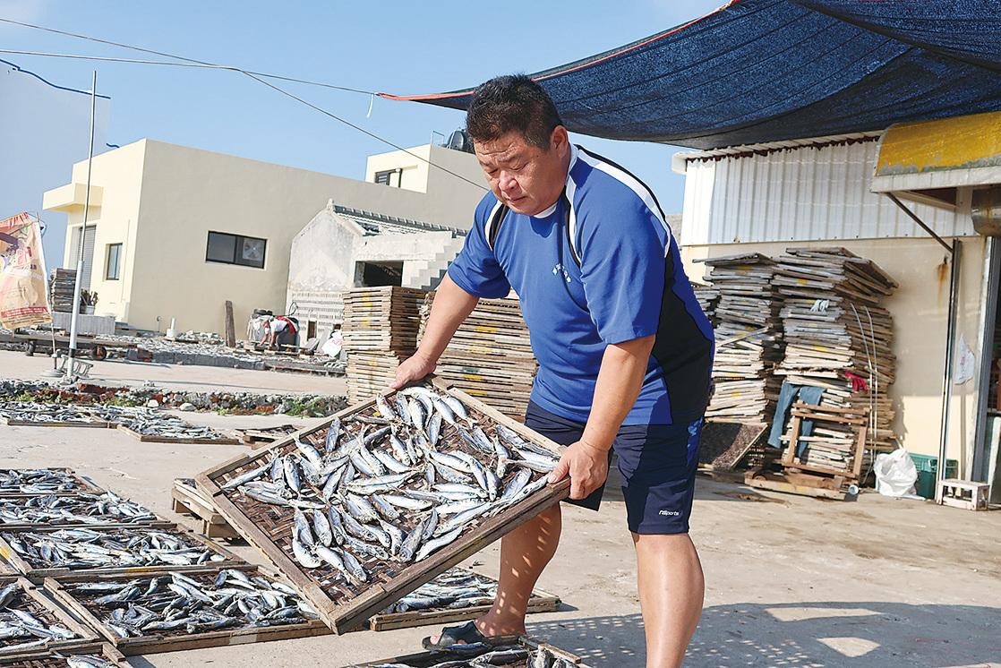 漁產加工行的負責人蔡武童示範曬魚。(徐曼沅/大紀元)