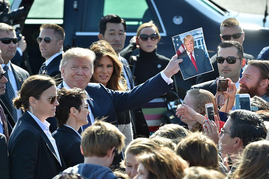2017年11月5日,東京橫田空軍基地,美國總統特朗普從接機的人群中拿到自己的照片,開心高舉起來。(KAZUHIRO NOGI/AFP/Getty Images)