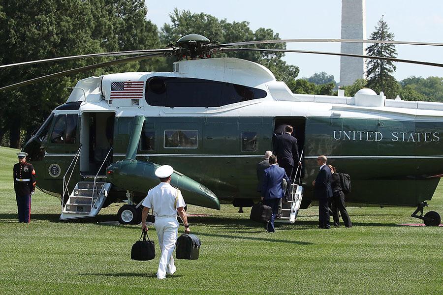 2017年8月4日,美國總統特朗普搭乘直昇機離開白宮,他的一名軍事隨從以右手替他提黑色公事包。(Mark Wilson/Getty Images)