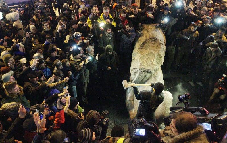 十月革命之後的百年共產歷史,充滿了血腥和罪惡。圖為2013年12月8日,烏克蘭首都基輔市中心的一座列寧塑像被推倒後,民眾拿槌子將其破壞。烏克蘭民眾從此在全國掀起推倒列寧雕像的棄共行動。(ANATOLI BOIKO/AFP)