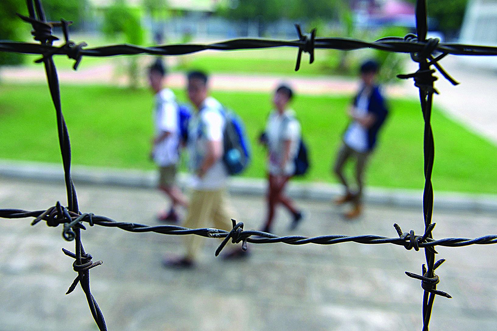 柬埔寨的吐斯廉屠殺博物館由前赤棉的集中營監獄改建而成,揭露共產暴政殘害人民的罪惡。圖為人們從該監獄的鐵絲網外面走過。(Getty Images)