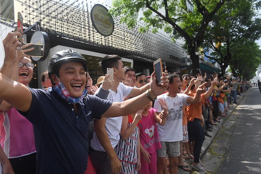 特朗普抵達越南時,受到當地民眾歡迎,很多民眾在街道兩邊迎接特朗普,打出歡迎標語、用手機拍照。(HOANG DINH NAM/AFP/Getty Images)