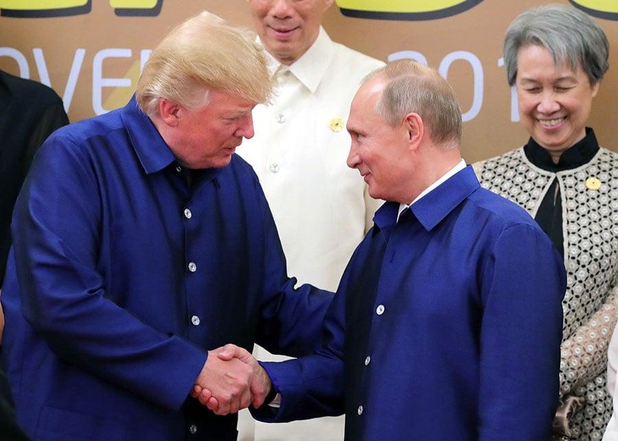 在亞太經合組織會議中,特朗普和穿同樣傳統服裝的普京握手。(MIKHAIL KLIMENTYEV/AFP/Getty Images)