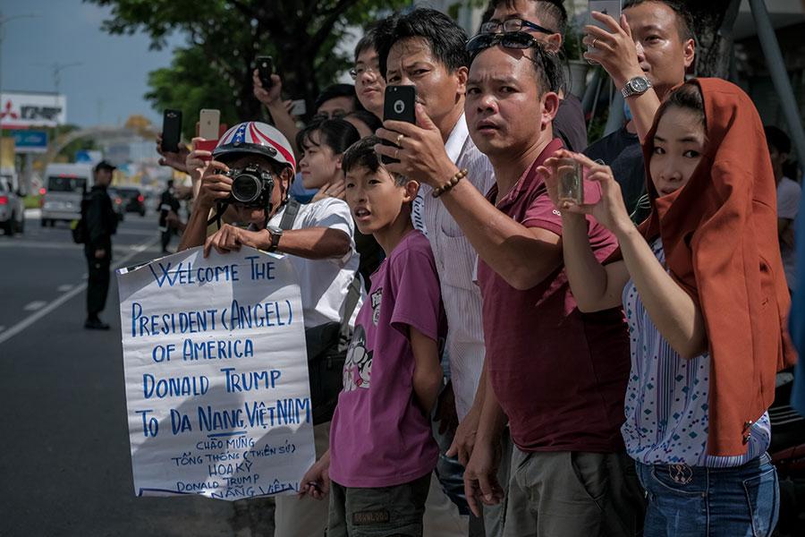 特朗普抵達越南時,也受到當地民眾歡迎,很多民眾在街道兩邊迎接特朗普,打出歡迎標語、用手機拍照。(Linh Pham/Getty Images)