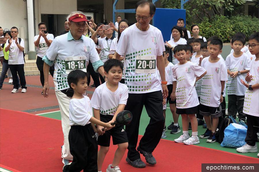 在校友梁錦松陪同下,由參加接力跑最後一棒的學生,交棒至英華書院校長鄭鈞傑。(英華家長提供)