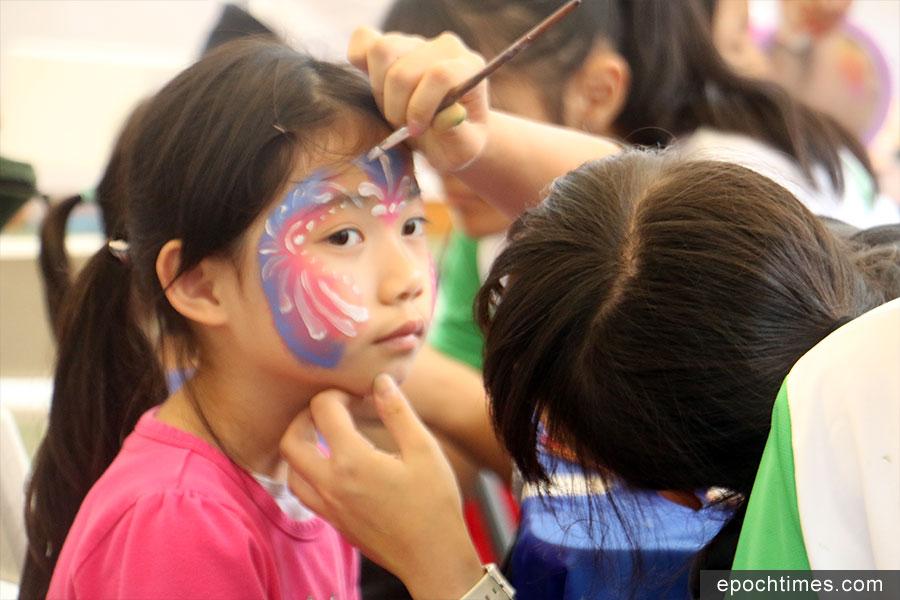 工作人員正在替小朋友畫上面部彩繪。(陳仲明/大紀元)