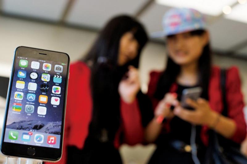 圖為2014年10月上海的兩位女孩在使用蘋果iPhone 6智能手機。(AFP)