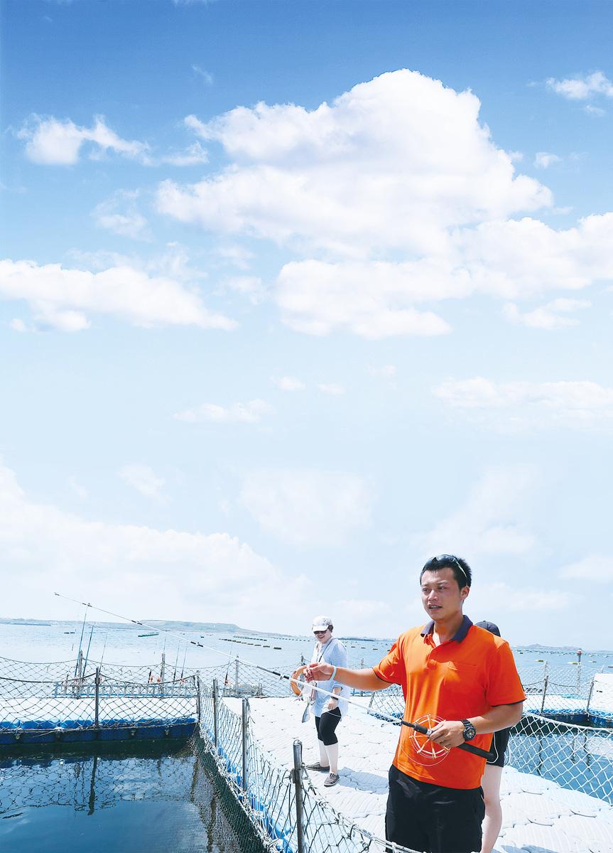 海上牧場的解說員示範海上釣魚。(徐曼沅/大紀元)