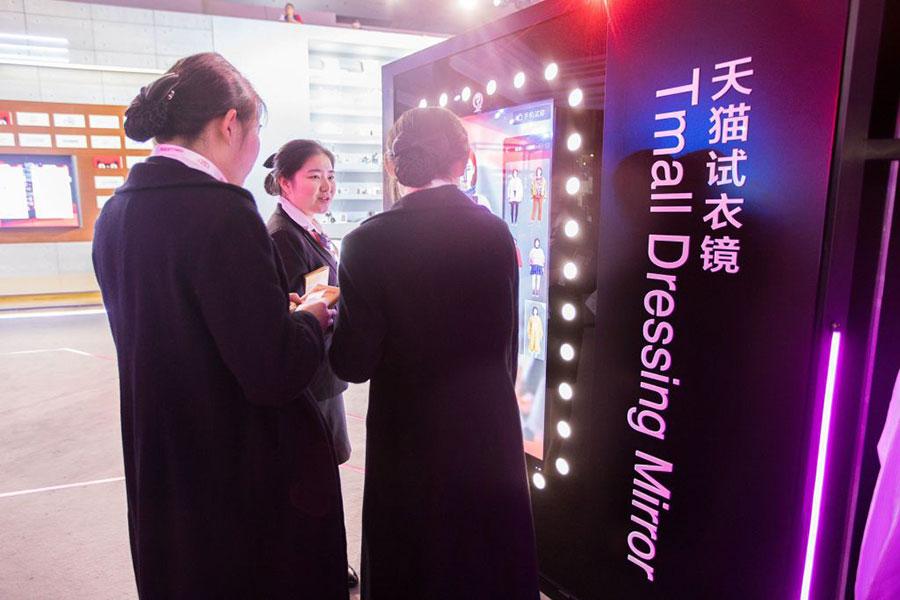 上海一個天貓電子屏幕前,3名女子在觀看屏幕上的貨物。(STR/AFP/Getty Images)