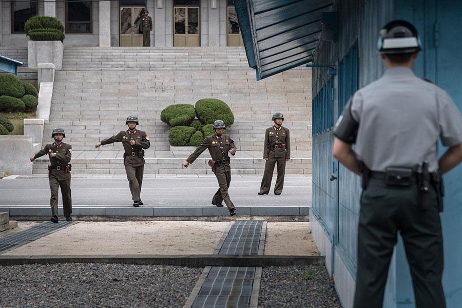 北韓一名士兵於11月13日越過板門店的非軍事區,向南韓投誠,但遭其他北韓士兵開槍射傷。圖為板門店一名南韓士兵面對幾名北韓士兵,此圖攝於2017年10月12日。(AFP)