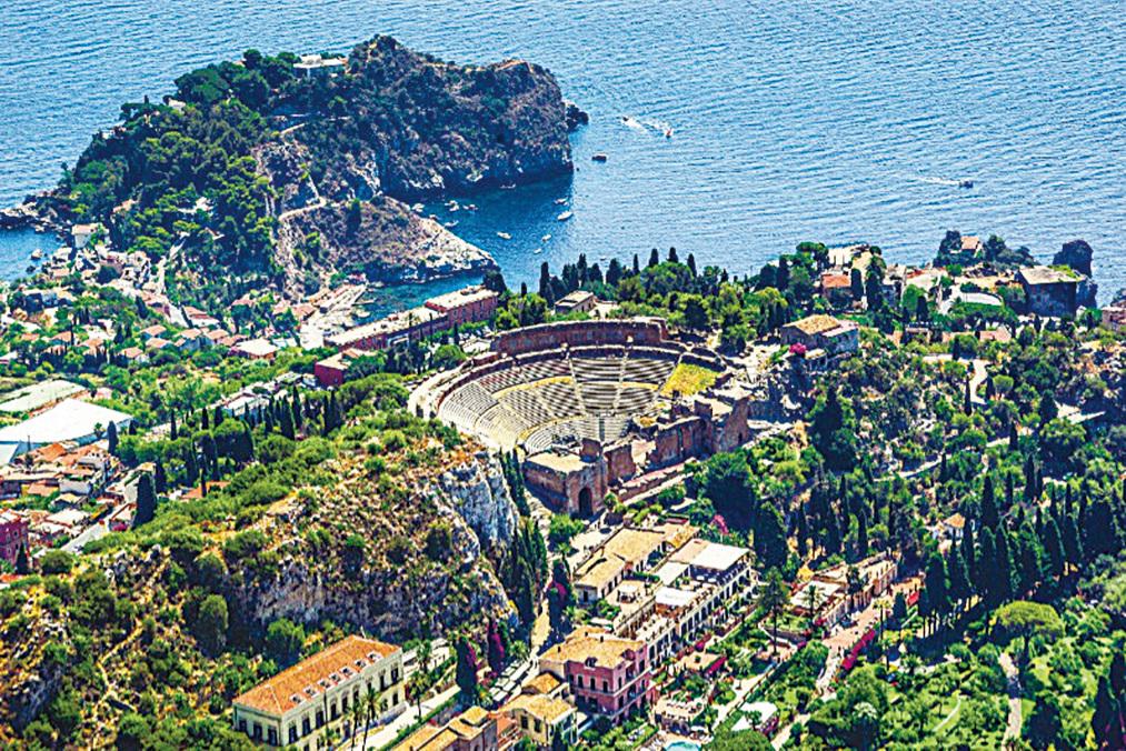 一座懸崖壁上的古希臘劇場,從山腳仰視,劇場彷彿一隻大碗懸於半空中。(shutterstock)