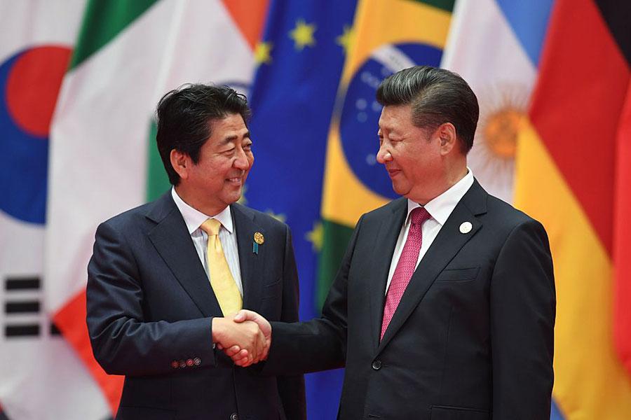 圖為安倍晉三和習近平和G20握手。(GREG BAKER/AFP/Getty Images)